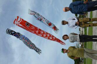 巨大こいのぼりを製作した山内平三郎さん(右から2人目)ら=3日、沖縄県糸満市の平和祈念公園
