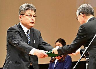 新聞協会賞の授賞式で表彰される編集局写真部の崎浜秀也部長(左)=26日午後、兵庫県神戸市・ポートピアホール
