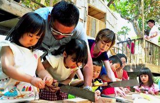 親子で廃材を使った工作をする親子連れ=3日、八重瀬町世名城・木の工房楽樹