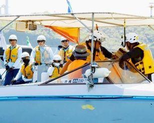 抗議する市民の船に乗り込む海上保安官=15日、名護市辺野古の海上