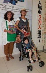 3万人目の来場者となった村上律子さん(左)と娘の北村紫乃さん(右)、孫の心湖ちゃん=25日、県立博物館・美術館