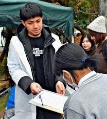 署名しに来た人に対応する元山仁士郎さん=16日、宜野湾市