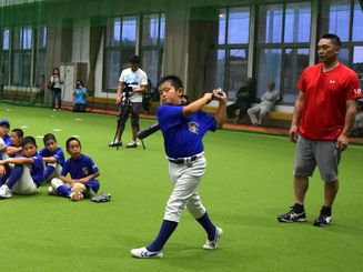 子どもたちにバッティングを指導する阿部慎之助選手(右)=伊江村多目的屋内運動場