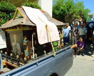 地域住民に見送られ、村立歴史民俗資料館に運ばれる龕=読谷村高志保