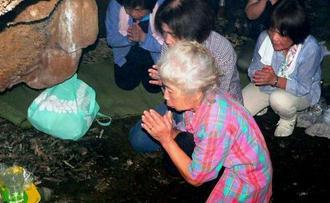 洞窟内で「孫がたくさん授かりますように」と手を合わせる参拝者ら=今帰仁村今泊