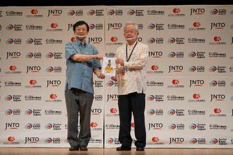 首里城再建への支援金を寄付するJATAの坂巻会長(左)=29日、宜野湾市の沖縄観光コンベンションセンター