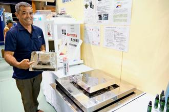 台風にも強い屋上点検口を開発したなか総合金物商会の國分司専務=県立武道館内の発明くふう展コーナー