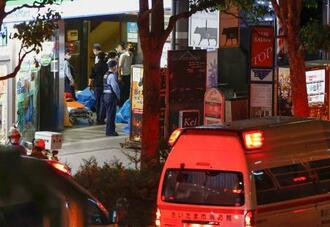 男が女性店員を人質に立てこもったビルの入り口で警戒する警察官ら=17日午後9時46分、さいたま市