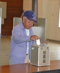 役場の建設位置を巡り、1票を投じる男性=竹富町大原地区、町離島振興総合センター