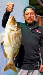 嘉手納海岸で63.5センチ、3.01キロのタマンを釣った仲吉章雄さん=7月27日