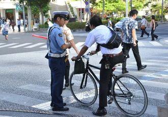 市民に自転車の適正利用を呼び掛ける警察官=16日午前7時58分、那覇市・県庁前交差点