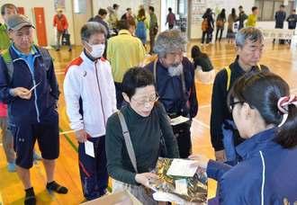 ナンバーカードを受け取る100キロ部門の参加者=宮古島市・下地体育館