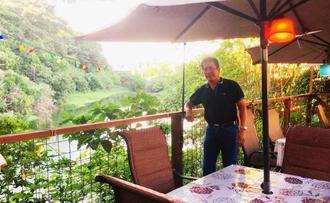 ペット同伴ができるテラスで、比謝川の自然の豊かさを語るオーナーの上江田さん