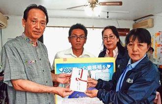 沖縄タイムス社の豊平良孝社長(左)から募金を受け取る、「らい君を救う会」の當山みゆき共同代表(右)と良生君の父の松島良道さん(右から3人目)ら=北谷町浜川の同会事務局