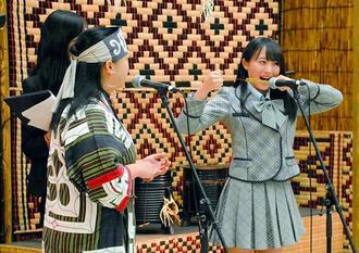 アイヌ民族の伝統楽器「ムックリ」(口琴)に挑戦するAKB48チーム8北海道代表の坂口渚沙さん(右)=3日、サンエー宜野湾コンベンションシティ