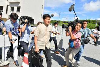 「撤回」の通知書を提出後、沖縄防衛局を後にする県土木建築部の松島良成土木整備統括監(中央)=31日午後3時29分、嘉手納町