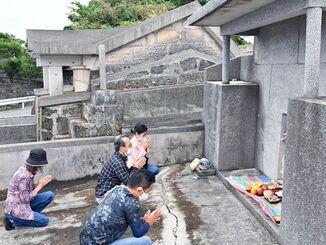 簡素化したシーミーで少人数で墓に手を合わせる親族=4日午前、那覇市・識名霊園