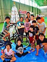 自転車をこいでライトやLED付きのツリーを点灯させた子どもたち=11月28日、浦添市運動公園の多目的屋内運動場