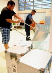 衆院選の投票日が1日繰り上がる南大東村では、投票箱を拭き記載台を組み立てる投票所設置作業が行われた=日、同村役場