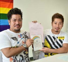 パートナーシップ登録申請書に記入を完了した入眞地順治さん(左)と安座間尚彦さん=11日午前、那覇市内