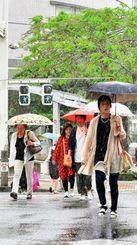 梅雨入りした沖縄地方。降り出した雨に傘を差して交差点を渡る人たち=16日午後、那覇市久茂地(渡辺奈々撮影)