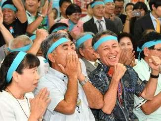 テレビで当確の速報が出た瞬間、両手で顔を覆う屋良朝博氏(中央)=21日午後8時、沖縄市安慶田の選挙事務所(田嶋正雄撮影)