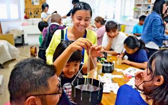 わくわくした表情でゾエトロープをのぞき込み、葛飾北斎の絵を使ったアニメーションを楽しむ子どもたち=19日、浦添市美術館