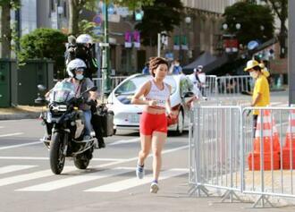 東京五輪マラソンのリハーサルで、コースを走る選手役のランナーと関係車両=1日、札幌市