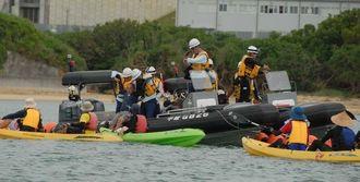 抗議の声をあげるカヌー隊のメンバーと、水中に入った市民をボートに引き上げる海保職員=30日午後0時9分、名護市辺野古沿岸