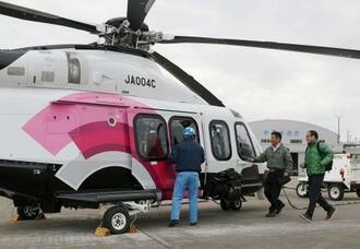 南海トラフ巨大地震に備えた名古屋市の民放4社の共同取材の訓練で、ヘリコプターに乗り込む担当者=14日午後、愛知県営名古屋空港