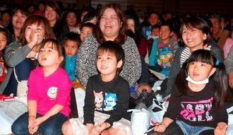 お笑いコントを見ながら交通安全を学ぶ園児たち=11日、那覇市・県立武道館