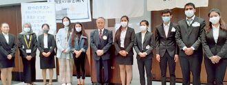 外国人留学生特別給付を受けた学生と大城会長(中央)=沖縄ハーバービューホテル