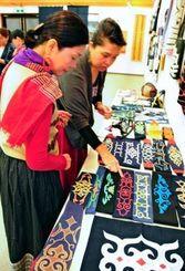 アイヌ伝統工芸作品展が始まり、多くの人が黒や濃紺の生地に曲線の描かれた衣服などを観賞している=15日、南風原文化センター