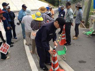 沖縄総合事務局の職員が歩道上に三角コーンを置いたことに、辺野古新基地建設に反対する市民らが抗議した=9日午前7時10分ごろ、名護市のキャンプ・シュワブ