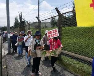「新基地建設を止めろ」と気勢を上げ行進する市民ら=21日午前10時20分、米軍キャンプ・シュワブゲート前