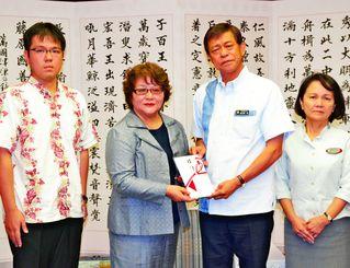 寄付金を贈呈した(左から)翁長雄一郎さんと樹子さん、受け取った謝花喜一郎副知事と大城玲子・子ども生活福祉部長=6日、県庁