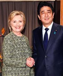 ヒラリー・クリントン氏(左)と握手する安倍首相=19日、ニューヨーク(共同)