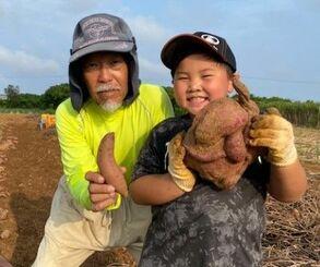 通常サイズの紅イモを持つ渡口勝さん(左)と、その約10倍重い紅イモを抱える勝斗さん=3月28日、石垣市宮良(提供)