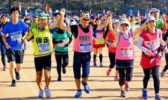 大久保篤志さんは伴走の渡名喜興俊さん、田中直子さんと3人で手をつないでゴールし初完走を飾った=1日、那覇市の奥武山陸上競技場