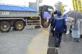 赤く濁った水が流れ出たことで、市民らの抗議を受ける大型車両=13日午前、沖縄県名護市安和