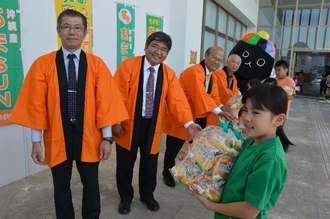あまSUNを使った「オレンジカスタードロール」を受け取る地域の子どもたち=4日、うるま市役所東棟玄関前