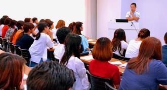 沖縄中央学園の学生を前に「名義貸しなどもうけ話に注意して」と呼び掛ける高良祐之弁護士(奥)=日、北谷町・同学園