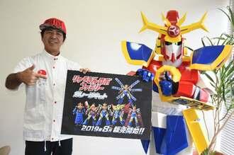「りゅうぎんロボ」ファミリーの6キャラクターのガレージキット発売をPRする琉球銀行の伊禮真メディア戦略室長(左)とりゅうぎんロボ=29日、沖縄タイムス社