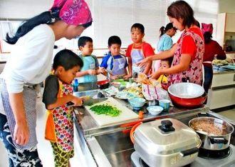 ネギを切ったり卵焼きを作ったりする子どもたち=23日、沖縄市社会福祉センター