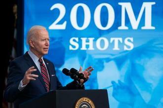 「2億回接種」の映像を背に演説するバイデン大統領=21日、ワシントン(AP=共同)