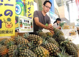 フェアを前にパイナップルなど特産品をブースに並べる関係者=3日午後、那覇市久茂地・タイムスビル