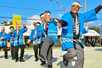 豊作、豊漁に感謝し、楽しそうな表情でクイチャーを踊る集落の男性たち=24日、宮古島市平良池間・池間島水浜広場