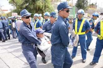 米軍キャンプ・シュワブゲート前で抗議活動する市民らを排除する機動隊員=28日、名護市辺野古