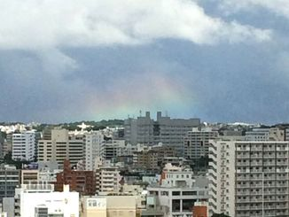 おもろまちの方向の上空に広がる、崩れたような形の虹=22日、那覇市久茂地の沖縄タイムス社から撮影