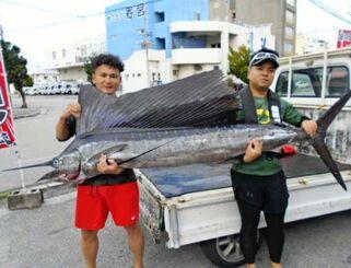 慶良間沖で252センチ、31.7キロのカジキを釣った大嶺太加樹さん(左)=20日